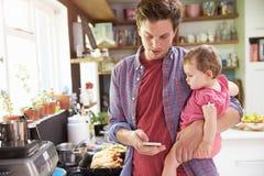 Telefone celular de Taking Selfie On do pai que guarda a filha nova Imagem de Stock