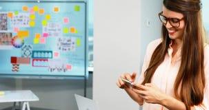 Telefone celular de utilização executivo fêmea no escritório vídeos de arquivo