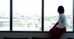 Telefone celular de utilização executivo fêmea perto da janela video estoque