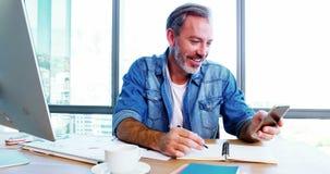 Telefone celular de utilização executivo masculino ao trabalhar na mesa video estoque
