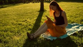 Telefone celular de utilização fêmea Redhaired no parque do verão video estoque