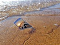 Telefone celular deixado cair na água do oceano fotografia de stock