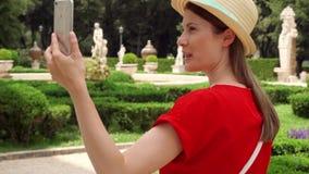 Telefone celular do uso da mulher no parque no movimento lento O turista tem o bate-papo video através do app na casa de campo Bo video estoque