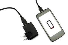 Telefone celular e carregador no fundo branco, isolado Fotografia de Stock Royalty Free