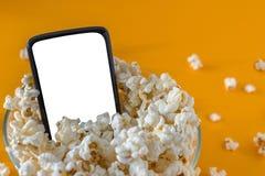 Telefone celular e pipoca em uma bacia, em uma tabela amarela, close-up Conceito da tecnologia fotografia de stock