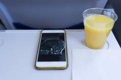 Telefone celular e suco de laranja fotos de stock royalty free