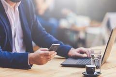 Telefone celular elegante da terra arrendada do homem com mão no teclado do portátil na cafetaria imagem de stock royalty free