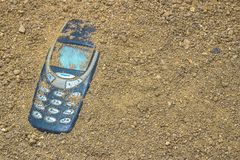 Telefone celular enterrado na areia cinzenta fotografia de stock