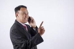 Telefone celular falador novo do homem de negócio, isolado no fundo branco Fotografia de Stock Royalty Free