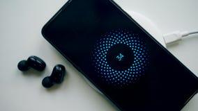 Telefone celular, fones de ouvido e um bloco de carregamento sem fio vídeos de arquivo
