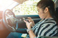 Telefone celular interior do toque da jovem mulher da beleza do fundo do carro Fotos de Stock