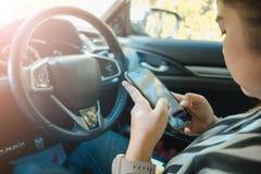 Telefone celular interior do toque da jovem mulher da beleza do fundo do carro Fotografia de Stock Royalty Free