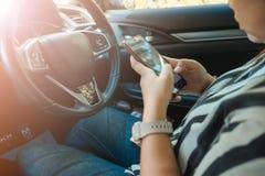Telefone celular interior do toque da jovem mulher da beleza do fundo do carro Fotos de Stock Royalty Free