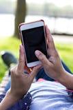 Telefone celular na mão da mulher em um deckchair na perspectiva da grama verde Hora de descansar fotografia de stock royalty free