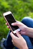 Telefone celular na mão da mulher em um deckchair na perspectiva da grama verde Hora de descansar fotos de stock