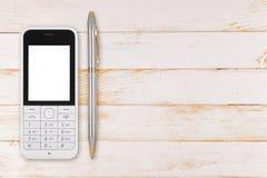 Telefone celular na tabela de madeira Foto de Stock Royalty Free