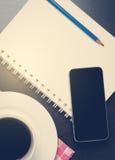 Telefone celular no caderno com café quente preto imagens de stock