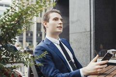 Telefone celular novo da terra arrendada do homem de negócios à disposição e olhando de lado imagem de stock