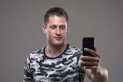 Telefone celular novo relaxado da terra arrendada do homem adulto e fotos ou selfie da tomada foto de stock royalty free
