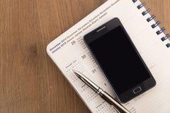 Telefone celular, pena e agenda imagens de stock royalty free