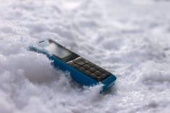 Telefone celular perdido que encontra-se na estrada na neve foto de stock royalty free