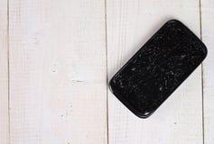 Telefone celular preto com a tela quebrada no fundo de madeira Fotografia de Stock Royalty Free
