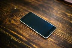 Telefone celular preto na tabela de madeira Imagem de Stock Royalty Free