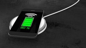 Telefone celular que recarrega na almofada de carregamento sem fio Fotos de Stock