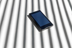 Telefone celular Smartphone atrás da sombra das barras fotos de stock royalty free
