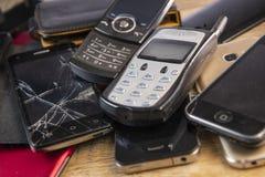 Telefone celular velho, quebrado e obsoleto no fundo de madeira imagens de stock