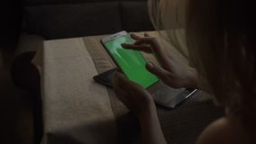 Telefone celular verde tocante da tela das mãos fêmeas no suco de laranja do fundo video estoque