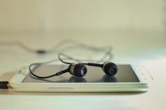 Telefone com fones de ouvido Fotografia de Stock