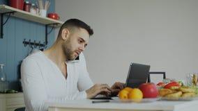 Telefone considerável do homem novo e laptop de fala da utilização que senta-se na cozinha após o café da manhã na manhã imagem de stock