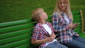 Telefone de assento Texting do banco do filho da mamã de uma comunicação vídeos de arquivo