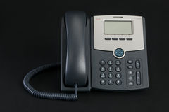 Telefone de Cisco VoIP isolado no fundo escuro Fotos de Stock Royalty Free