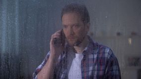 Telefone de fala chocado do homem atrás da janela chuvosa, notícia terrível, morte relativa filme