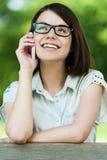 Telefone de fala da mulher consideravelmente nova Foto de Stock Royalty Free