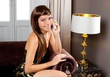 Telefone de fala da mulher da forma da elegância no sofá Imagens de Stock