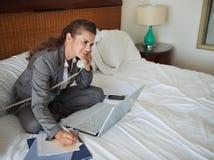 Telefone de fala da mulher de negócio na sala de hotel foto de stock royalty free
