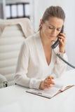 Telefone de fala da mulher de negócio no escritório Imagem de Stock Royalty Free