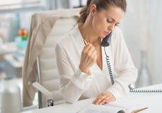 Telefone de fala moderno da mulher de negócio no escritório Fotografia de Stock Royalty Free