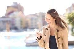 Telefone de observação de riso da mulher feliz Imagem de Stock Royalty Free