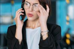 Telefone de pesquisa de defeitos da conversação da mulher de negócio fotografia de stock