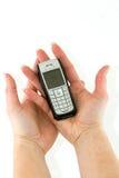 Telefone de pilha nas mãos da mulher Imagem de Stock Royalty Free