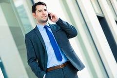 Telefone de utilização exterior do homem de negócios seguro imagem de stock royalty free
