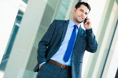 Telefone de utilização exterior do homem de negócios seguro imagem de stock