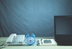 Telefone, despertador, bloco de notas e portátil do escritório na mesa do negócio Imagens de Stock