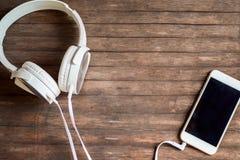 Telefone do écran sensível na tabela Fones de ouvido e smartphone brancos no fundo de madeira Foto de Stock Royalty Free