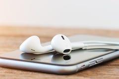 Telefone do close up e dispositivo do fones de ouvido na tabela imagem de stock royalty free