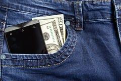 Telefone do dinheiro nas calças de brim Imagens de Stock